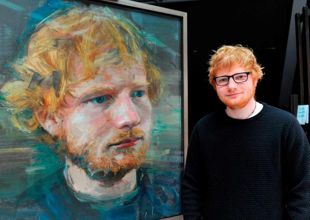 Ed Sheeran with the portrait by Belfast artist Colin Davidson at the National Portrait Gallery in London. Photo: PA