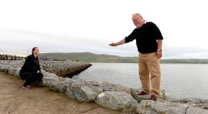 Kevin Flannery and Grace McGratten showing the height of the proposed flood protection harbour wall opposite Dingle Oceanworld in County Kerry which will take away some of the scenic view of the harbour. Photo: Don MacMonagle