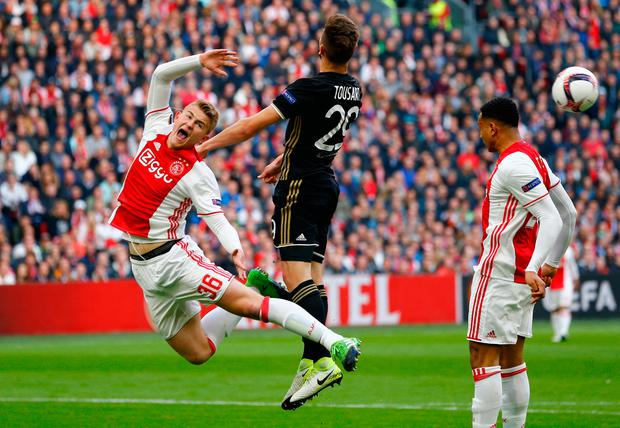 Ajax's Matthijs de Ligt goes down after an aerial challenge with Lucas Tousart. Photo: Reuters
