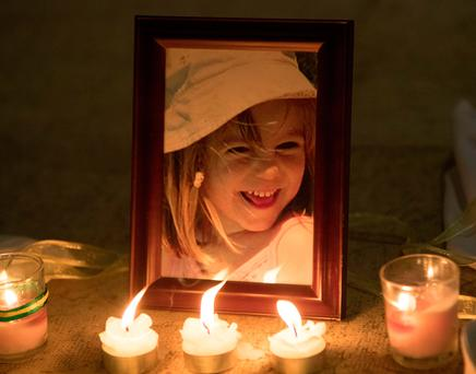 Candles are placed next to a photo of Madeleine McCann inside the Church of Nossa Senhora da Luz in Praia Da Luz, Portugal, where a special service was held to mark the 10th anniversary of her disappearance. Photo: Steve Parsons/PA Wire