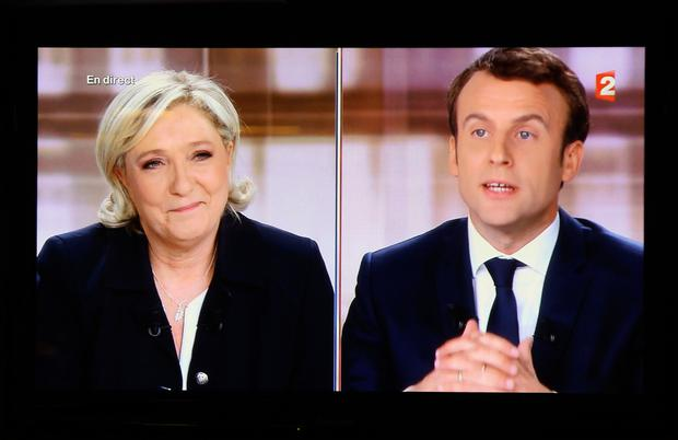 A television screen shows the live broadcast television debate with French centrist presidential candidate Emmanuel Macron and Marine Le Pen