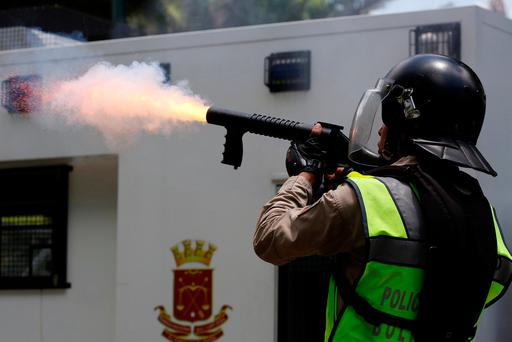 A riot police officer fires tear gas at opposition supporters during a protest against President Nicolas Maduro in Caracas. Photo: Reuters