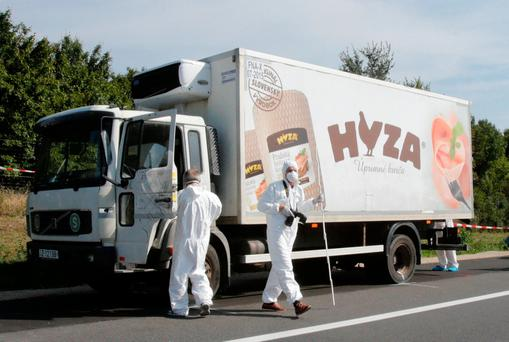 Forensic police officers inspect a parked truck in which migrants were found dead, on a motorway near Parndorf, Austria