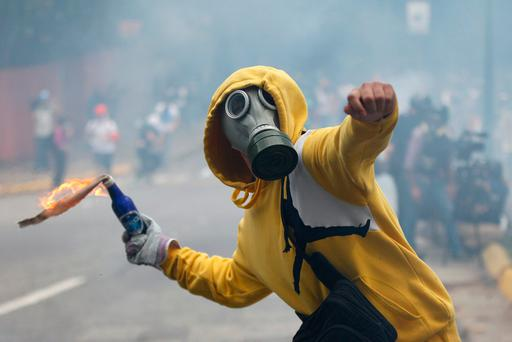 A demonstrator aims a fire bomb during an opposition May Day march in Caracas, Venezuela (AP Photo/Ariana Cubillos)
