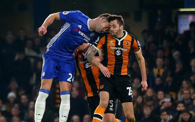 Gary Cahill of Chelsea bangs heads with Ryan Mason