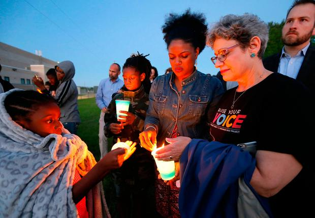 Hope Waters, left, her brother Jeremiah, center rear, and their mother Yulise, center right, light candles with Linda Abrasion Evans, right, during a candle light vigil for Jordan Edwards in Balch Springs, Texas, Thursday, May 4, 2017. The prosecutor's office investigating the death of a black teenager who was shot by a Dallas-area police officer had once filed a complaint over that officer's aggressive behavior, according to records obtained Thursday by The Associated Press. (AP Photo/Tony Gutierrez)