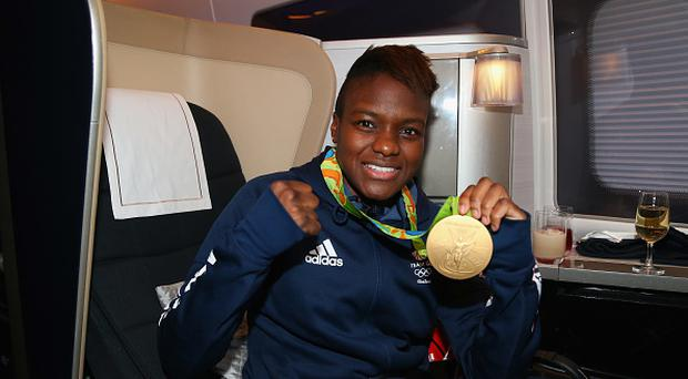 Nicola Adams of Great Britain poses with her gold medal during the Team GB flight back from Rio on British Airways flight BA2016 on August 22, 2016 in Rio de Janeiro, Brazil. (Photo by Alex Livesey/Getty Images for British Airways)