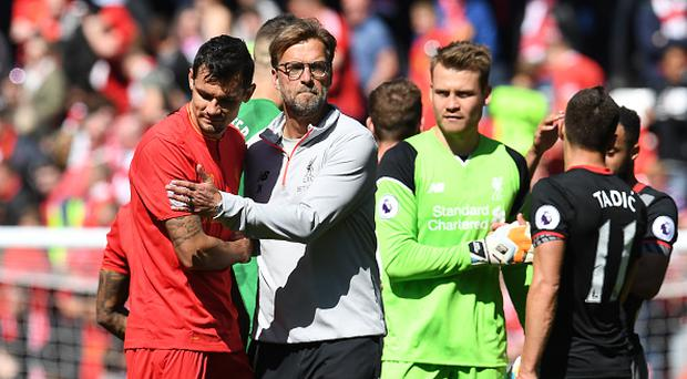 Liverpool's German manager Jurgen Klopp (C) embraces Liverpool's Croatian defender Dejan Lovren after the English Premier League football match between Liverpool and Southampton at Anfield in Liverpool, north west England on May 7, 2017. / AFP PHOTO / Paul ELLIS
