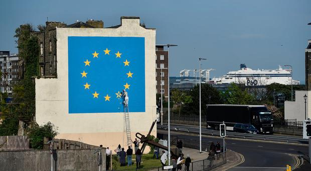 An artwork attributed to street artist Banksy, depicting a workman chipping away at one of the 12 stars on the flag of the European Union, is seen on a wall in the ferry port of Dover, Britain May 7, 2017. REUTERS/Hannah McKay