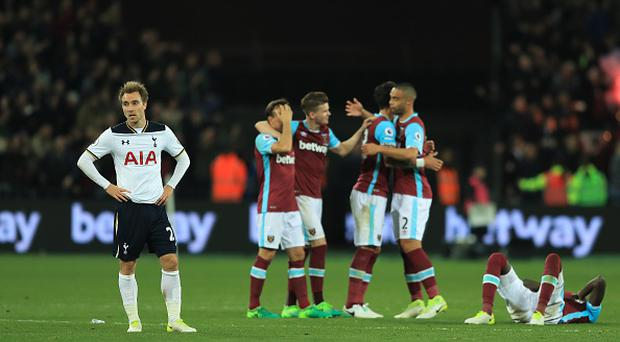 A dejected Christian Eriksen of Tottenham Hotspur looks on as West Ham players celebrate their team's 1-0 victory during the Premier League match between West Ham United and Tottenham Hotspur at the London Stadium on May 5, 2017 in Stratford, England. (Photo by Richard Heathcote/Getty Images)