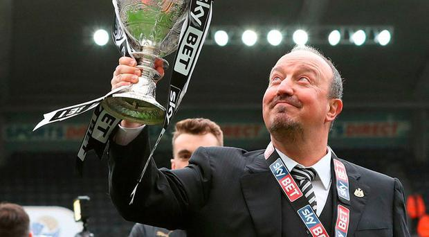 Newcastle United manager Rafa Benitez celebrates with the Sky Bet Championship trophy after the final whistle. Photo: Owen Humphreys/PA Wire