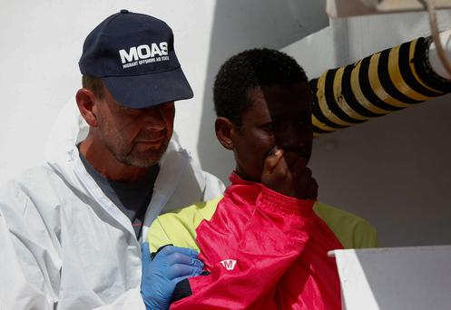 The brother of a migrant who was shot and killed by Libyan smugglers watches as the body is taken ashore in Sicily. Photo: REUTERS