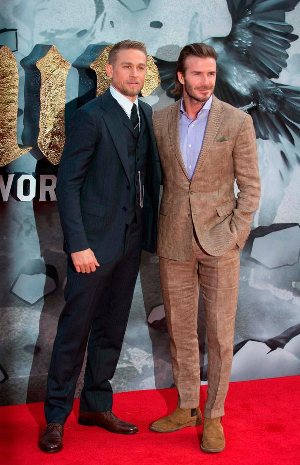 British actor Charlie Hunnam (L) and former England football captain David Beckham (R) pose for a photograph upon arrival at the European Premiere of