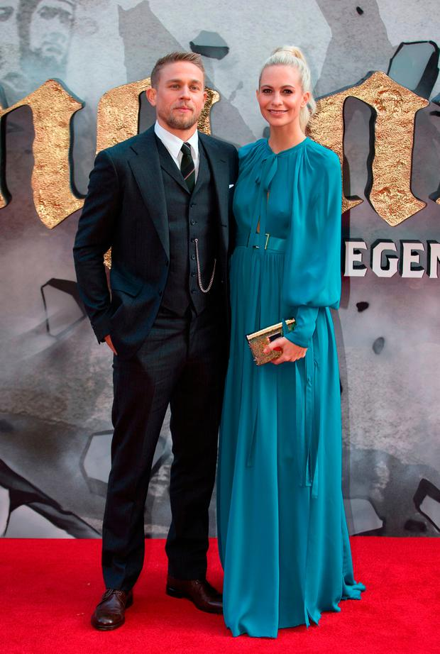 British actor Charlie Hunnam (L) and British model Poppy Delevingne pose for a photograph upon arrival at the European Premiere of