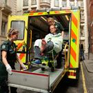 BBC cameraman Giles Wooltorton is loaded into an ambulance after the car carrying Jeremy Corbyn ran over his foot Photo: Yui Mok/PA Wire