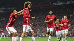 Belgian midfielder Marouane Fellaini (2nd L) celebrates with teammates after scoring the opening goal of the UEFA Europa League semi-final, second-leg football match between Manchester United and Celta Vigo at Old Trafford stadium in Manchester, north-west England, on May 11, 2017. / AFP PHOTO / Miguel RIOPA
