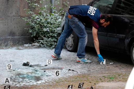 An Italian plain clothes policeman inspects the site where an explosive device blasted off near a post office in Rome. (AP Photo/Gregorio Borgia)