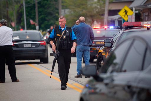 Law enforcement officials gather outside the scene of a shooting outside the Pine Kirk nursing home in Kirkersville, Ohio on Friday, May 12, 2017. Tom Dodge/The Columbus Dispatch via AP)