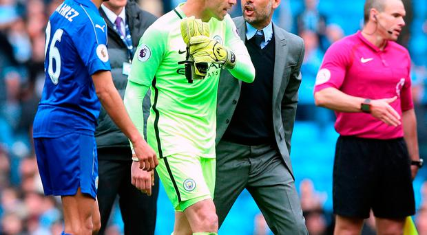 Manchester City manager Pep Guardiola celebrates with goalkeeper Willy Caballero