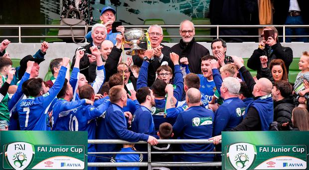 Secretary of Sheriff FC, Brian Dunleavy lifts the cup as the players celebrate after winning the FAI Junior Cup Final in association with Aviva and Umbro between Sheriff FC and Evergreen FC at the Aviva Stadium in Dublin. Photo by Matt Browne/Sportsfile