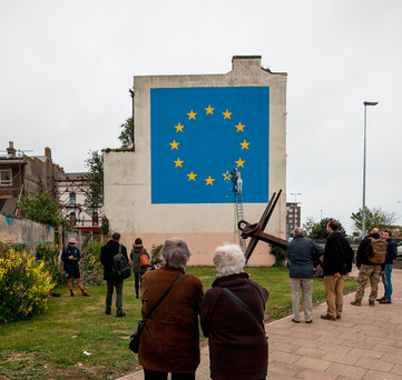 People in Dover look at a mural by street artist Banksy depicting a EU flag being chiseled by a workman on the side of a disused building Photographer: Simon Dawson/Bloomberg
