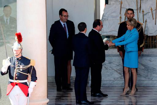 Former French President Francois Hollande (2ndR) holds hands with Brigitte Trogneux (R) as President Emmanuel Macron (2ndL) looks on at the end of their handover ceremony at the Elysee Palace in Paris, France, May 14, 2017. REUTERS/Patrick Kovarik/Pool