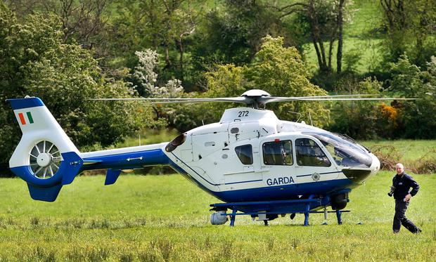 A forensic officer boards the Garda chopper to take some aerial photos at the scene in Mullagh, Co Cavan. Photo: Steve Humphreys
