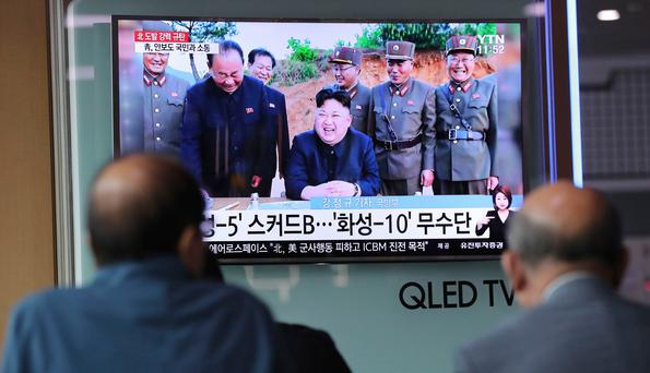 People watch a TV news program showing an image of North Korean leader Kim Jong Un, published in the country's Rodong Sinmun newspaper, at Seoul Railway station in Seoul. (AP Photo/Lee Jin-man)