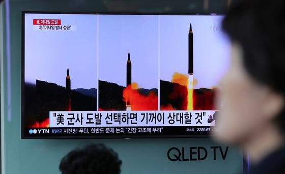 A woman walks by a TV news program showing images of North Korean missile launch, published in the country's Rodong Sinmun newspaper, at Seoul Railway station in Seoul (AP Photo/Lee Jin-man)