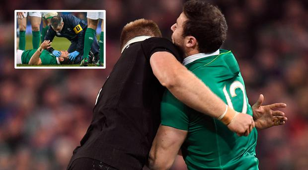 Robbie Henshaw of Ireland is tackled by Sam Cane