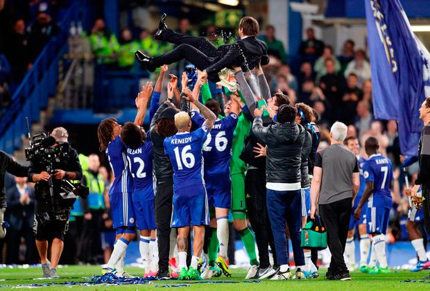 Chelsea manager Antonio Conte is lifted up by his players