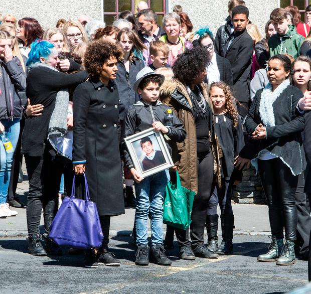 The funeral mass of Conor Wilmot. Conor's mum Irina, sister Melinie and his brother Ross who is holding a framed photograph of Conor. Photograph Liam Burke Press 22