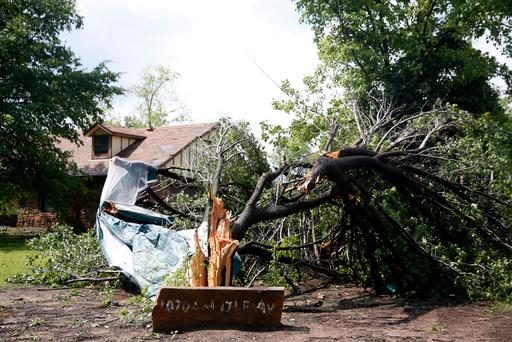 A tree lies damaged from a storm in Owasso, Okla, Thursday, May 11, 2017. The National Weather Service said a tornado touched down in the Tulsa suburb of Owasso Thursday and a possible tornado struck near Perkins, about 45 miles northeast of Oklahoma City. Damage was reported to roofs and trees, but there are no reports of injuries. (Ian Maule/Tulsa World via AP)