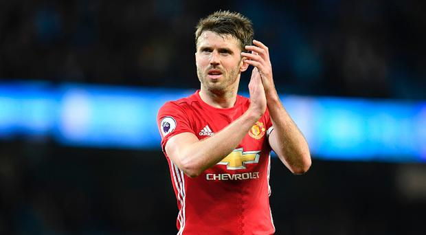 Manchester United's English midfielder Michael Carrick applauds their fans at the end of the English Premier League football match between Manchester City and Manchester United at the Etihad Stadium in Manchester, north west England, on April 27, 2017. / AFP PHOTO / Paul ELLIS