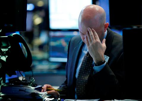 Specialist trader Jay Woods works at his post on the floor of the New York Stock Exchange