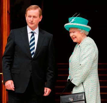 Taoiseach Enda Kenny greets Queen Elizabeth at Government Buildings during the second day of her State Visit to Ireland in May 2011. Photo: Julien Behal/PA