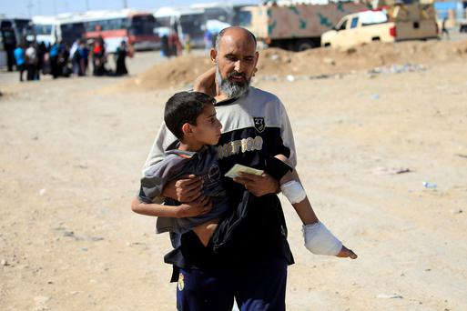 A displaced Iraqi father and son flee their home in Mosul. Photo: Alaa Al-Marjani/Reuters