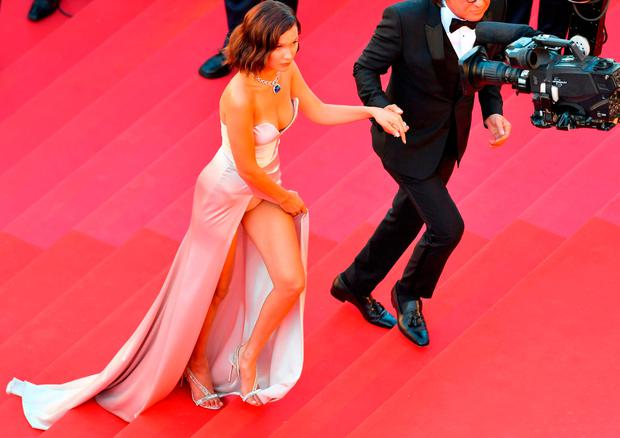 US model Bella Hadid (L) and her father Mohamed Hadid arrive on May 17, 2017 for the screening of the film 'Ismael's Ghosts' (Les Fantomes d'Ismael) during the opening ceremony of the 70th edition of the Cannes Film Festival in Cannes, southern France. / AFP PHOTO / LOIC VENANCELOIC VENANCE/AFP/Getty Images
