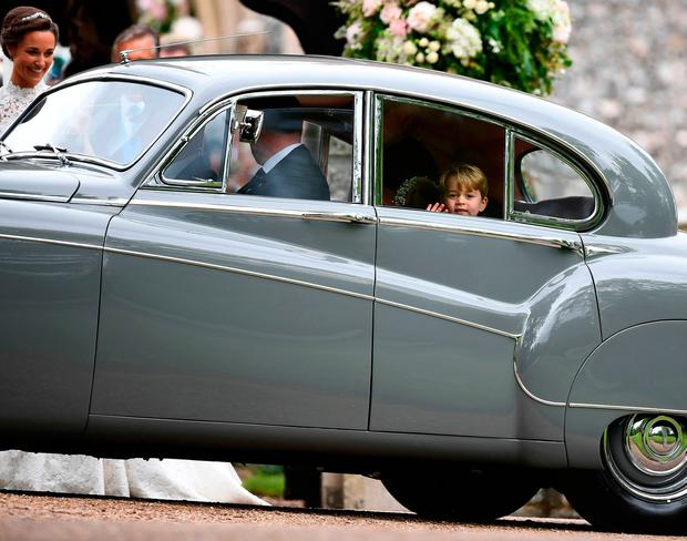 Britain's Prince George (R) waves as he leaves in a car after attending the wedding of his aunt, Pippa Middleton (L), to James Matthews at St Mark's Church in Englefield