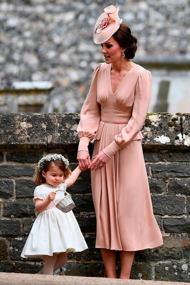 The Duchess of Cambridge with her daughter Princess Charlotte outside St Mark's church in Englefield, Berkshire, following the wedding of Pippa Middleton and James Matthews.