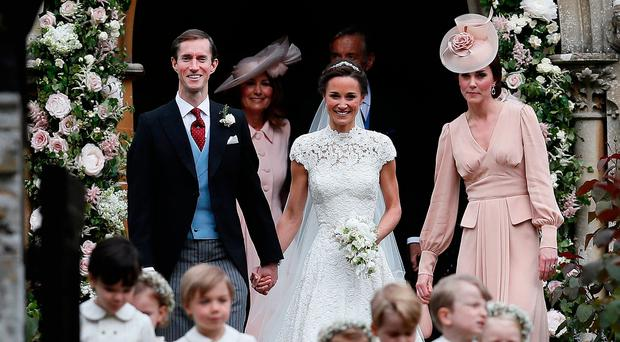 Pippa Middleton and James Matthews smile as they are joined by Catherine Duchess of Cambridge right after their wedding at St Mark's Church