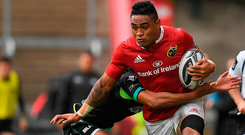 Francis Saili of Munster is tackled by Keelan Giles of Ospreys. Photo: Sportsfile