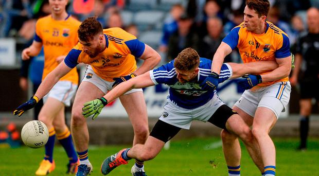 Denis Booth of Laois battles with Longford's Larry Moran and Liam Connerton. Photo: Daire Brennan/Sportsfile