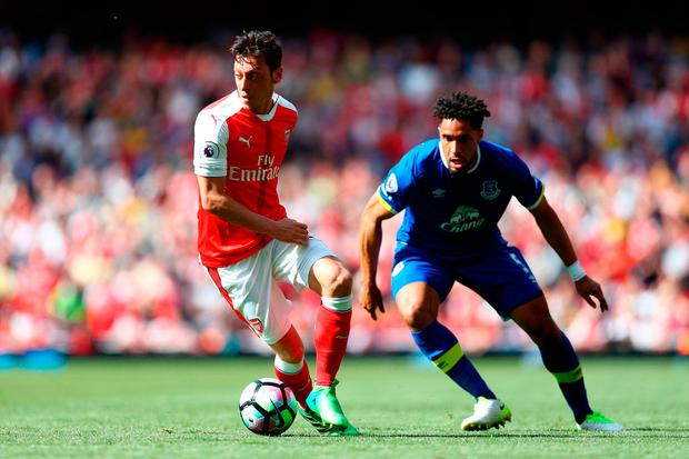 Mesut Ozil of Arsenal and Ashley Williams of Everton in action. Photo by Paul Gilham/Getty Images