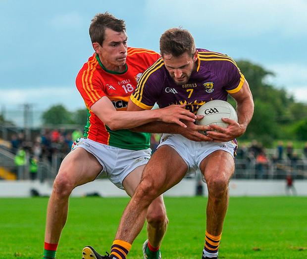 Wexford's Brian Malone in action against Carlow's Sean Gannon. Photo: Ramsey Cardy/Sportsfile