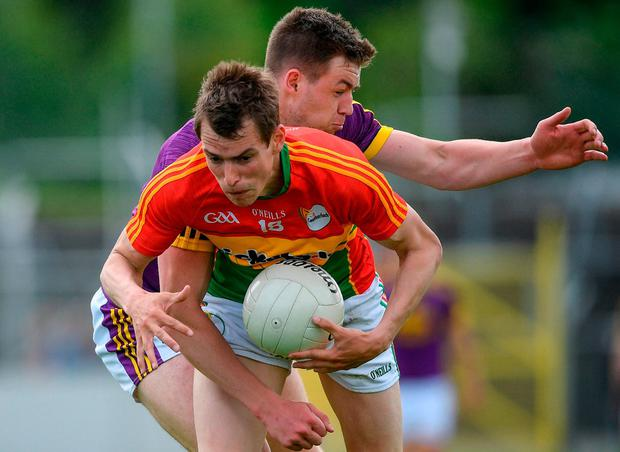Carlow's Sean Gannon is tackled by Wexford's Naomhan Rossiter. Photo: Ramsey Cardy/Sportsfile