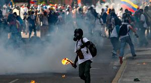 A masked protester winds-up to throw a petrol bomb during clashes with government security forces in Caracas, Venezuela, Saturday, May 20, 2017. (AP Photo/Ariana Cubillos)