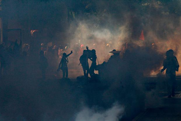 Protesters are silhouetted in clouds of tear gas launched by government security forces during clashes in Caracas, Venezuela, Saturday, May 20, 2017. (AP Photo/Ariana Cubillos)