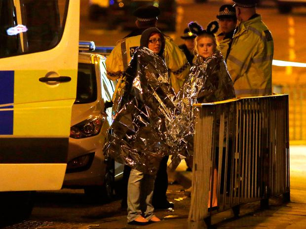 Two women wrapped in thermal blankets stand near the Manchester Arena. Photo: Reuters