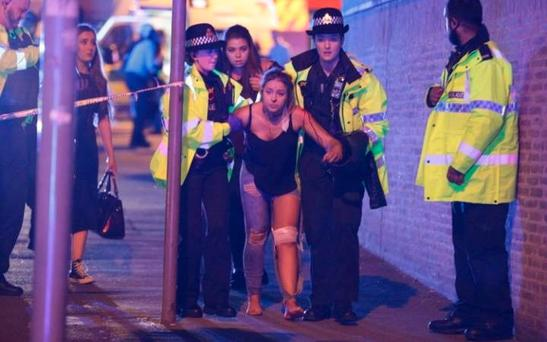 An injured woman is helped out of the Manchester Arena after last night's blast at a gig by Ariana Grande, which left 19 dead